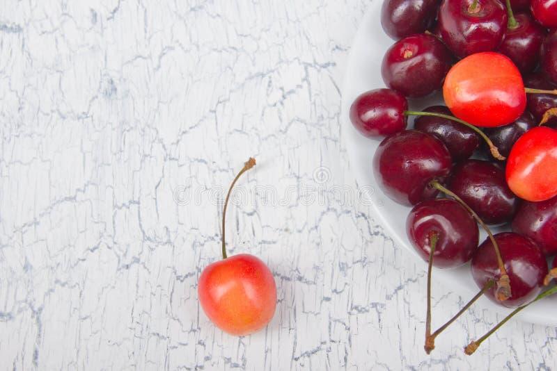 Cereza fresca del diverso verano en un cuenco en la tabla de madera rústica Antioxidantes, dieta del detox, frutas orgánicas Visi foto de archivo libre de regalías