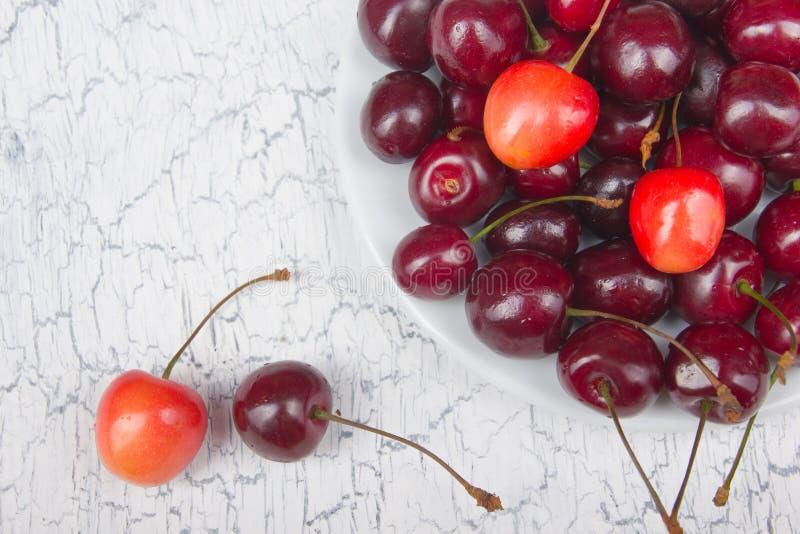 Cereza fresca del diverso verano en un cuenco en la tabla de madera rústica Antioxidantes, dieta del detox, frutas orgánicas Visi fotos de archivo libres de regalías