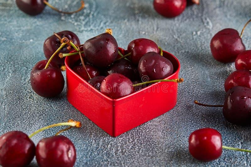 Cereza fresca o cereza dulce con descensos del agua con un corazón rojo Concepto para el d?a de tarjetas del d?a de San Valent?n foto de archivo
