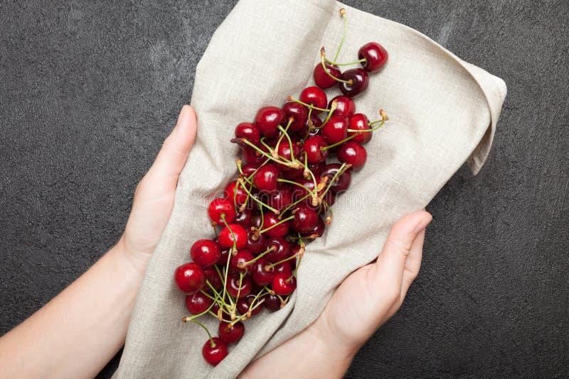 Cereza fresca y del jugo en la tabla en manos foto de archivo libre de regalías