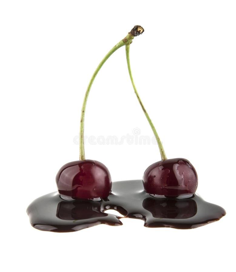 cereza roja en el chocolate líquido aislado en blanco fotos de archivo