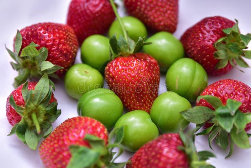 Cereza y ciruelo verdes de la fresa con las hojas verdes aisladas en el fondo blanco imagen de archivo libre de regalías