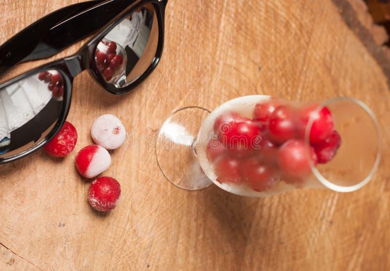 Cerezas congeladas en los vidrios y las gafas de sol en una tabla de madera foto de archivo