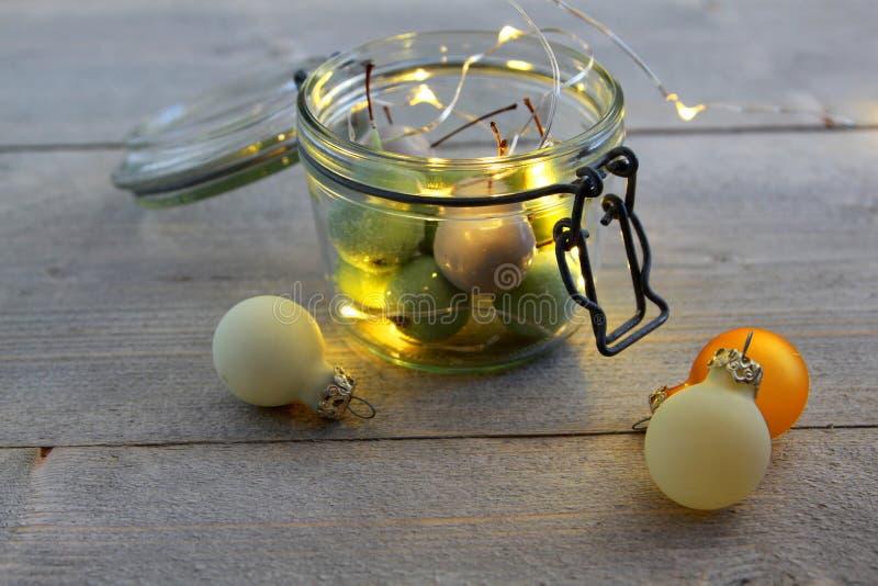 Cerezas de la cera en vidrio del tarro con las luces LED y las bolas de la Navidad fotografía de archivo libre de regalías
