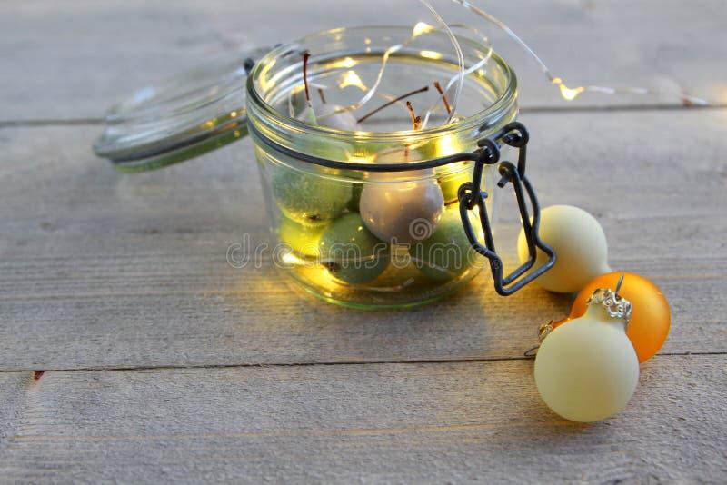 Cerezas de la cera en vidrio del tarro con las luces LED y las bolas de la Navidad imágenes de archivo libres de regalías