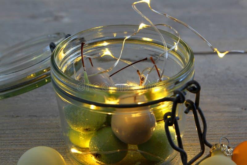 Cerezas de la cera en vidrio del tarro con las luces LED y las bolas de la Navidad foto de archivo