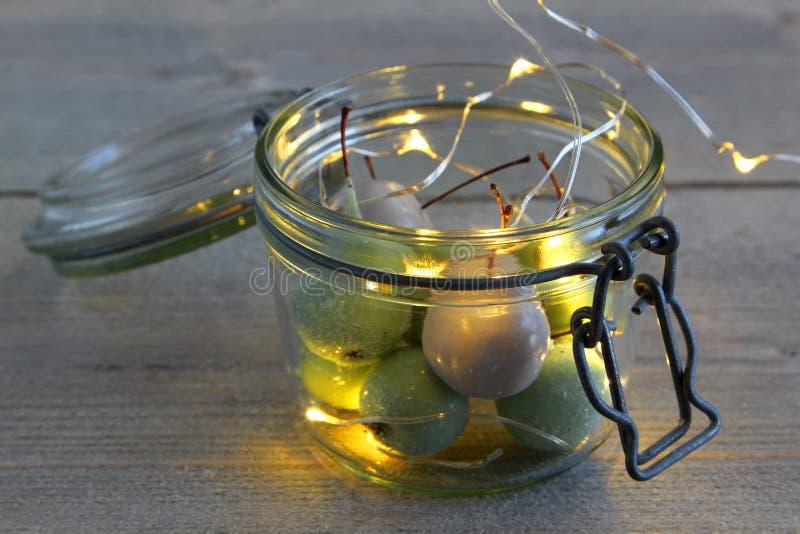 Cerezas de la cera en vidrio y luces LED del tarro foto de archivo libre de regalías
