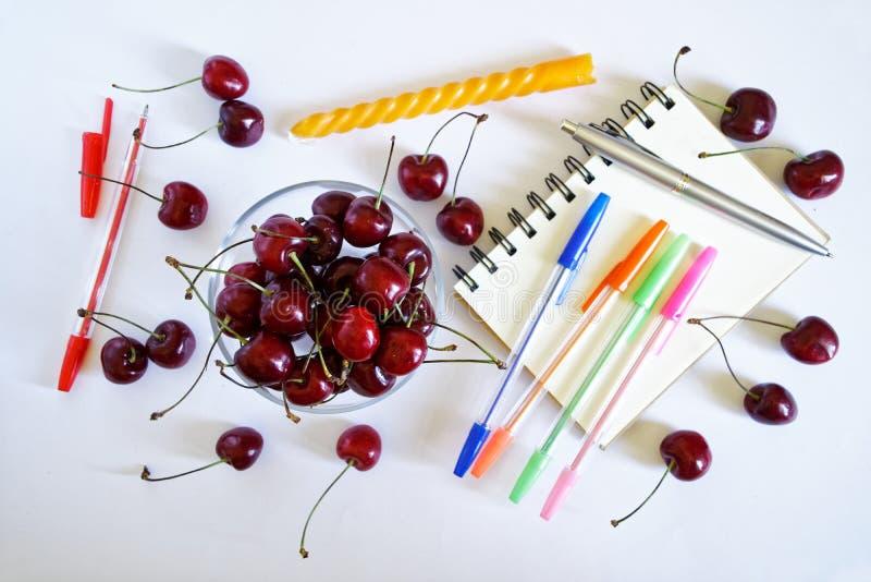 Cerezas dulces en una taza de cristal redonda en un fondo ligero al lado de un cuaderno, de plumas multicoloras y de una vela fes foto de archivo