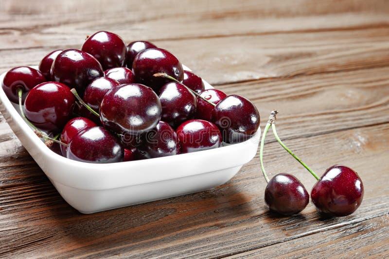 Cerezas dulces jugosas maduras frescas rojas en una placa blanca en un fondo de madera imagen de archivo libre de regalías