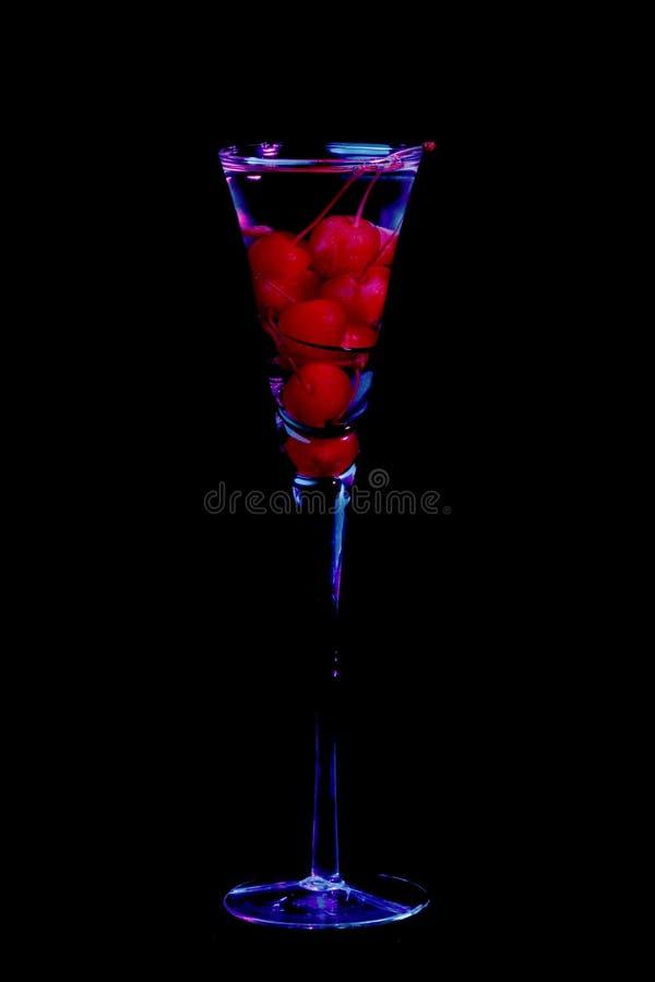Cerezas en vidrio del champán imagen de archivo