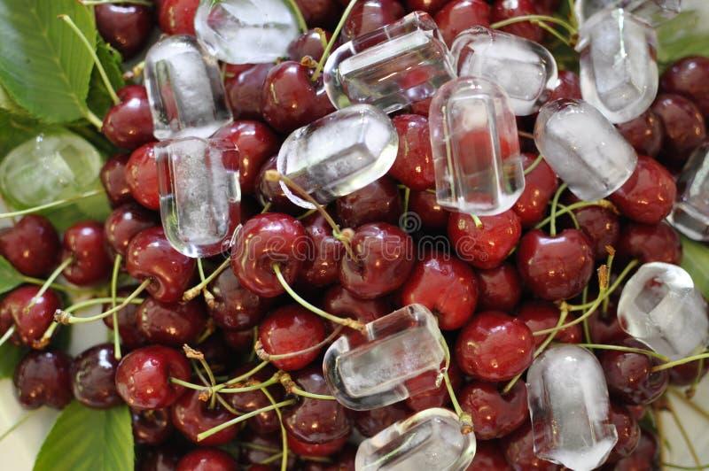 Cerezas frescas con los cubos de hielo imágenes de archivo libres de regalías
