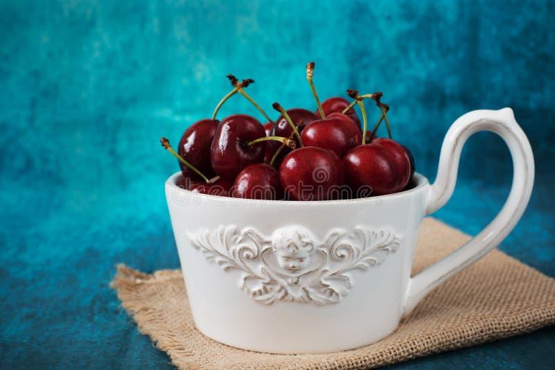 Cerezas frescas en un cuenco blanco, una taza grande Frutas frescas, ensalada de fruta Fondo para una tarjeta de la invitación o  fotografía de archivo libre de regalías