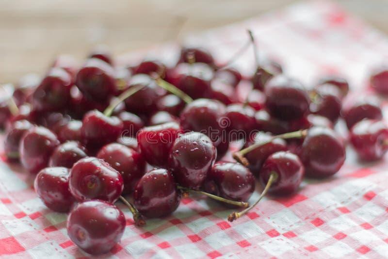Cerezas frescas, maduras, jugosas que mienten en la tabla, foco selectivo, profundidad del campo baja fotografía de archivo