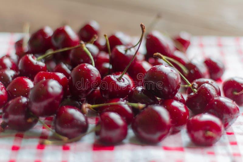 Cerezas frescas, maduras, jugosas que mienten en la tabla, foco selectivo, profundidad del campo baja fotos de archivo libres de regalías