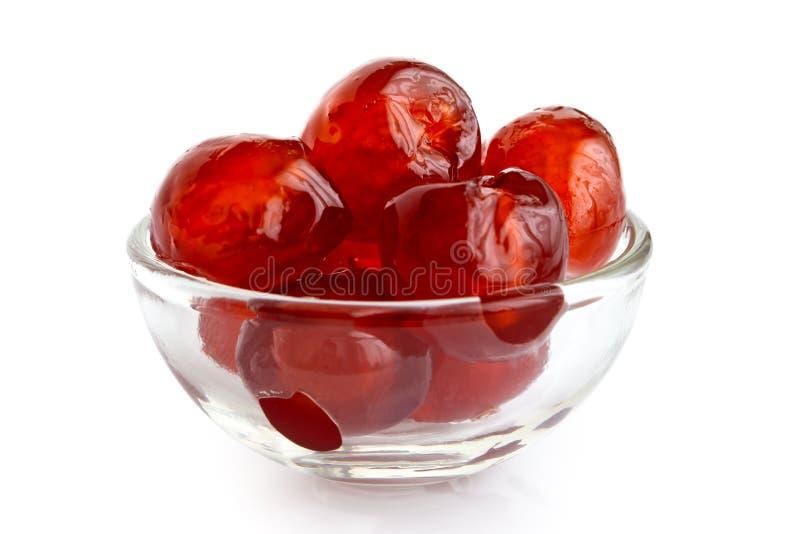 Cerezas glace rojas en el bol de vidrio aislado en blanco fotos de archivo