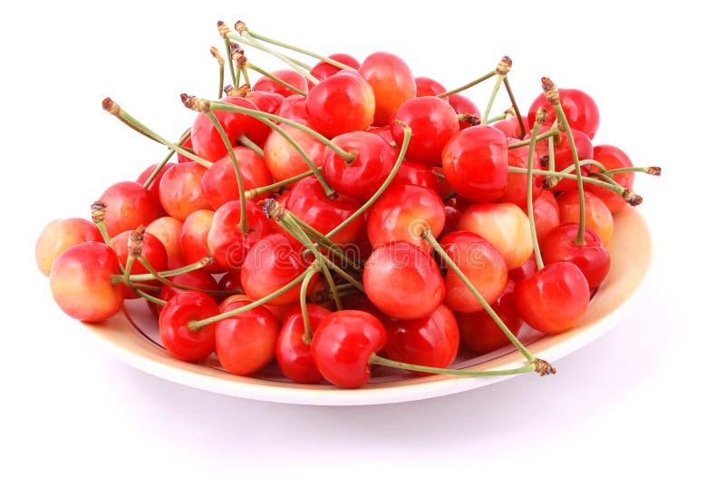 Cerezas rojas en una placa foto de archivo