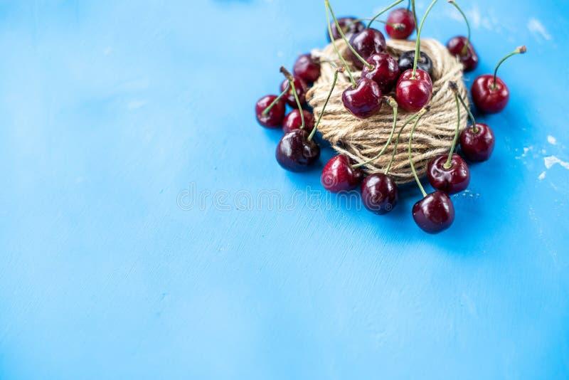 Cerezas rojas sabrosas aisladas en fondo azul del caramelo Bayas dulces rojas Cereza roja jugosa madura Foto de la comida antioxi foto de archivo
