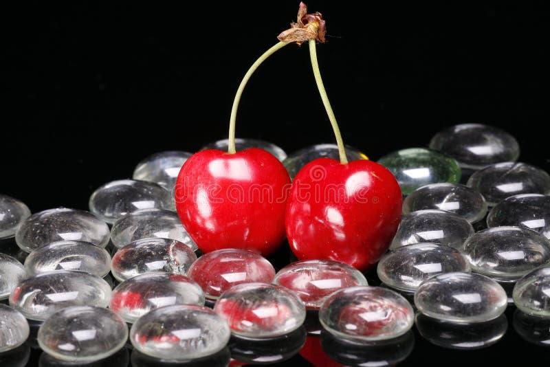 Cerezas rojas y granos de cristal fotos de archivo