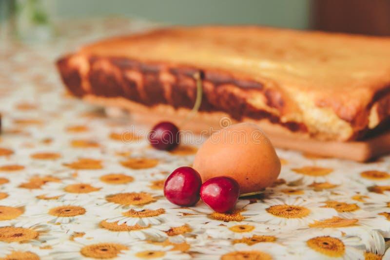 Cerezas y albaricoque con el pastel de queso hecho en casa en un tablero rebanador de madera en el fondo fotografía de archivo libre de regalías