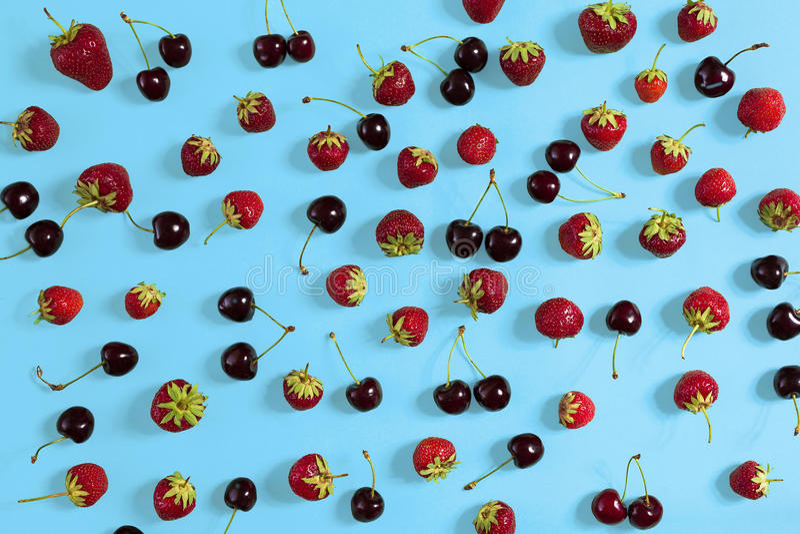 Cerezas y fresas frescas en el fondo azul, visión superior imagen de archivo