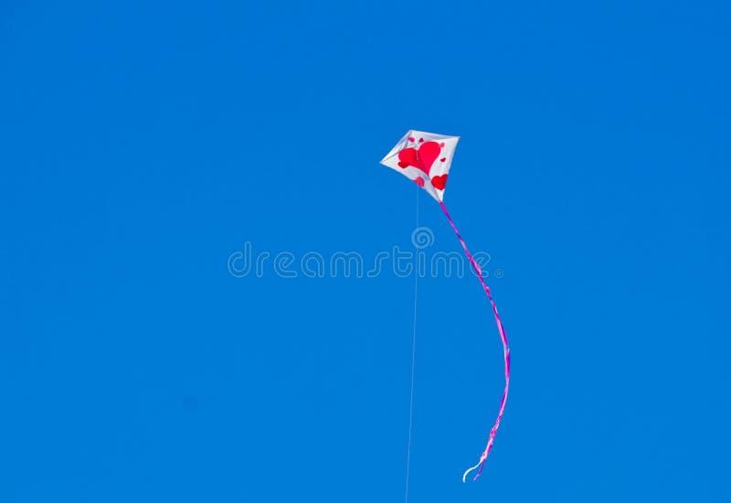 Cerf-volant avec les coeurs rouges volant dans le ciel photos libres de droits