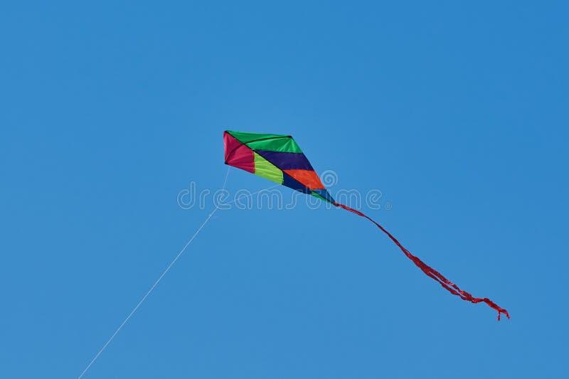 Cerf-volant coloré de jouet contre le ciel bleu images stock