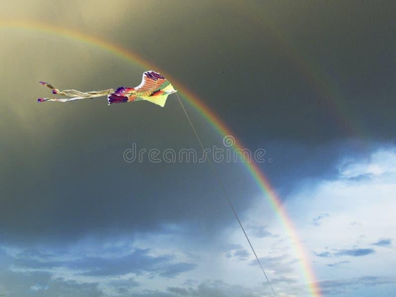 Cerf-volant lumineux sous forme d'oiseau dans le ciel avec un arc-en-ciel et des nuages foncés en été photos libres de droits