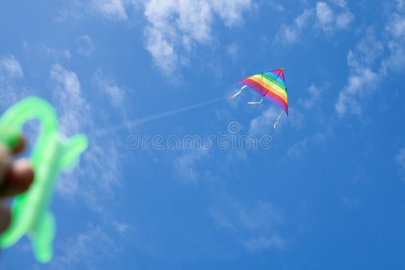 Cerf-volant multicolore sur le fond du ciel bleu avec des nuages images libres de droits