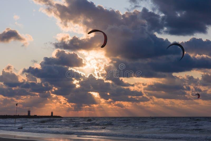 Cerf-volant surfant dans le coucher du soleil à la plage photo stock