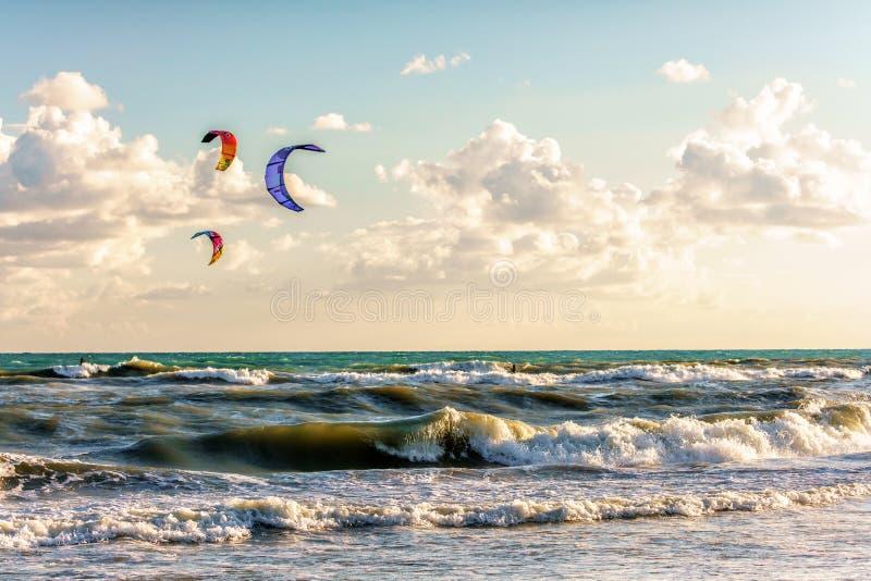 Cerfs-volants de tour de Kitesurfers par les vagues surfantes de la Mer Noire orageuse à la plage sablonneuse par Anapa photographie stock libre de droits