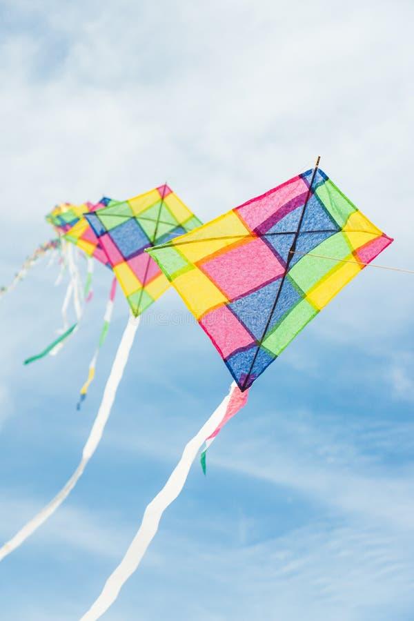 Cerfs-volants multicolores colorés volant en ciel bleu photo libre de droits