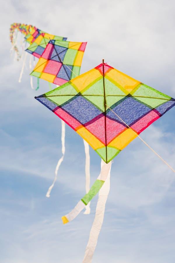 Cerfs-volants multicolores colorés volant en ciel bleu photos libres de droits