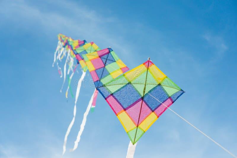 Cerfs-volants multicolores colorés volant en ciel bleu image stock