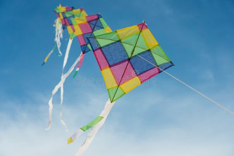 Cerfs-volants multicolores colorés volant en ciel bleu photographie stock