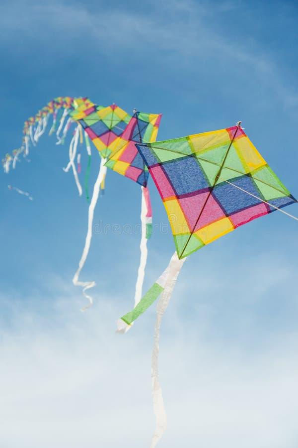 Cerfs-volants multicolores colorés volant en ciel bleu photos stock