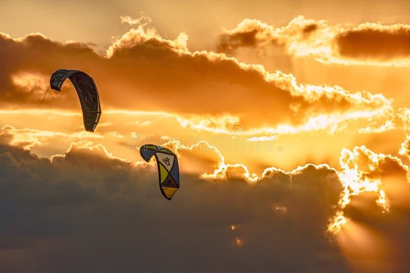 Cerfs-volants volant en air sur le fond scénique de ciel de coucher du soleil Le kitesurf est activité extérieure de bord de la m images stock