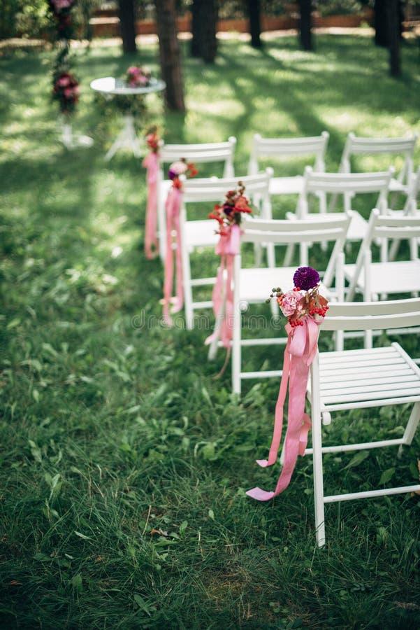 Cerimônia de casamento exterior, cadeiras decoradas com as fitas na grama foto de stock royalty free