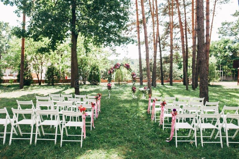 Cerimônia de casamento exterior, cadeiras decoradas com flores foto de stock royalty free