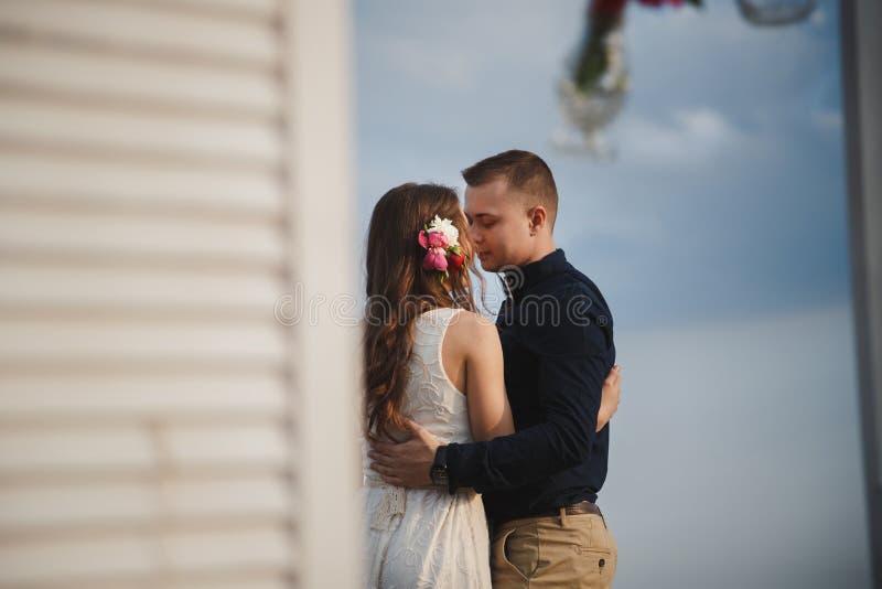 A cerimônia de casamento exterior da praia, o noivo de sorriso feliz à moda e a noiva são altar próximo ereto do casamento na cos fotos de stock royalty free