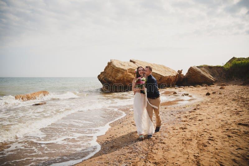 A cerimônia de casamento exterior da praia perto do mar, o noivo de sorriso feliz à moda e a noiva estão beijando e estão tendo o foto de stock