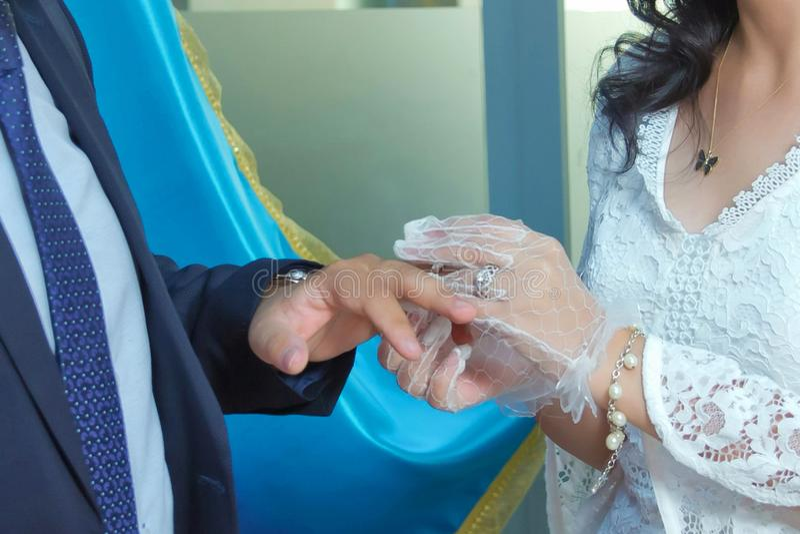 Cerimônia de casamento tradicional na igreja O padre está pondo o anel dourado sobre o dedo do noivo Pares felizes do casamento n imagens de stock