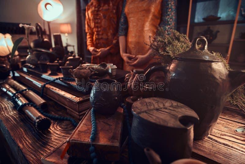 Cerimônia de chá chinesa Pares de mestres do chá que estão ao lado de uma tabela com um grupo para fazer o chá e os acessórios no fotografia de stock royalty free