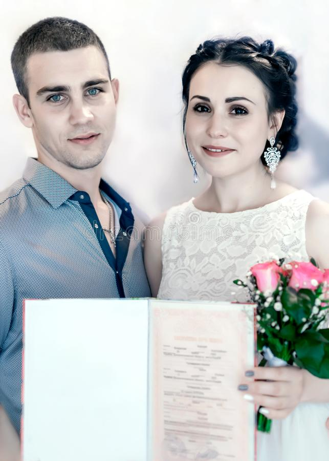 Cerimônia oficial do registro de união no escritório de registro em Ucrânia Noivos bonitos novos dos pares que guardam um março imagens de stock