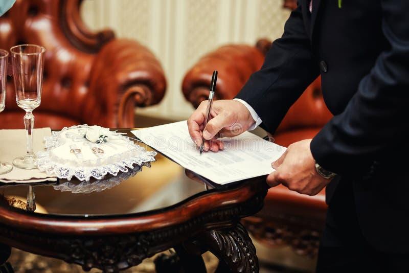 Cerimonia di cerimonia nuziale Equipaggi il contratto di matrimonio di firma, il primo piano, lo sposo s fotografie stock libere da diritti