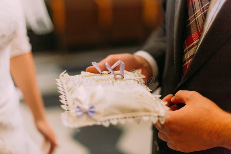 Cerimonia di nozze classica Anelli dorati su un cuscino nella vecchia chiesa immagine stock