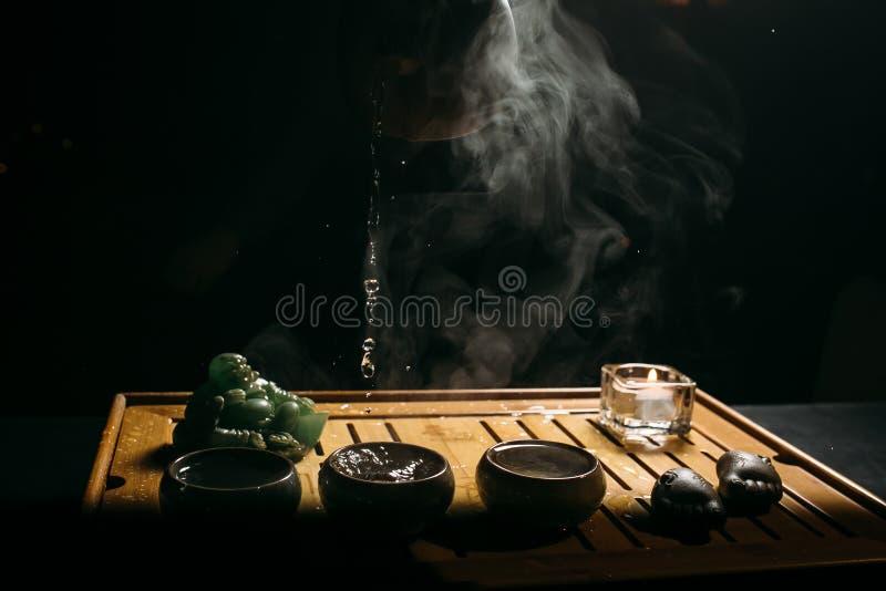 Cerimonia di tè L'uomo versa il tè cinese caldo nella tazza di tè immagini stock libere da diritti