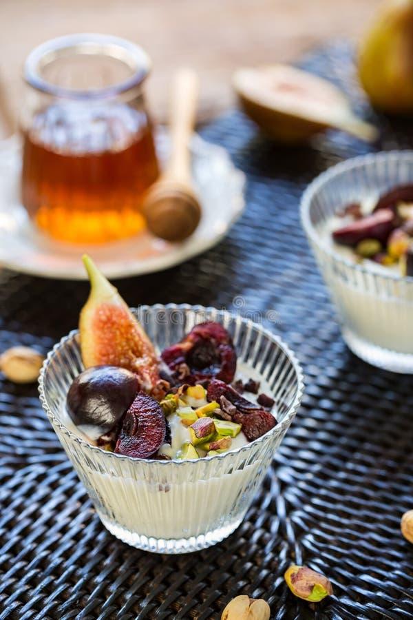 Cerise, figue et Pisttachio sur le yaourt grec photos stock