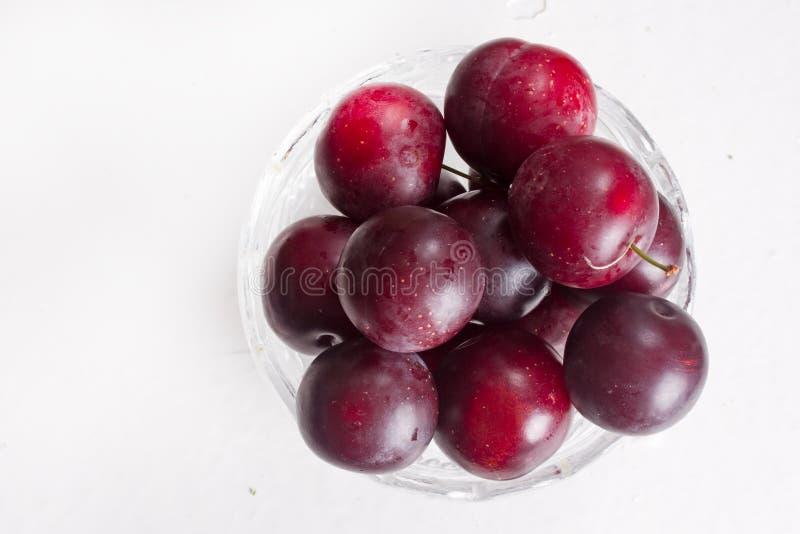 Cerise-prunes juteuses dans un bol en verre photographie stock libre de droits