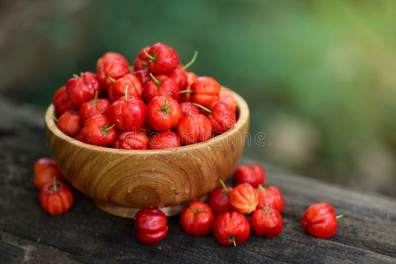 Cerise rouge d'Acerola dans la cuvette en bois photo stock