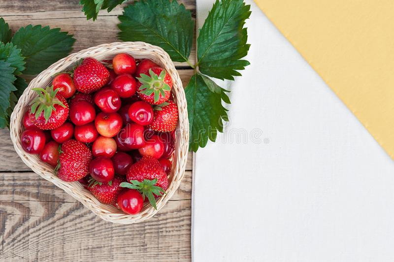 Cerises fraîches et fraises mûres rouges d'un plat blanc photo stock